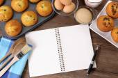 Fresh muffins with blank notebook — Foto Stock