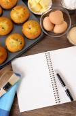 Fresh muffins with blank notebook — ストック写真