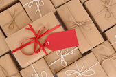 Parcels with red gift tag — Stock Photo