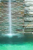 Waterfall decorate in the pool and green water tone — Stock Photo