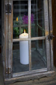 White candle in decorative lantern with flowers in the background — Fotografia Stock