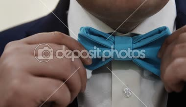 The man adjusts his blue bow tie close up — Stock Video