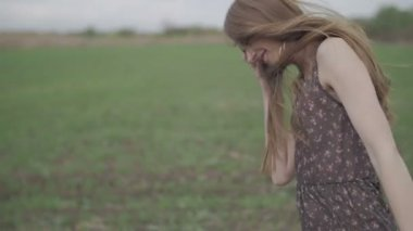 Beautiful girl with ribbon in dark dress with floral print run across the green field while wind blowing her hair camera rotate follow from shoes to hair middle shot ungraded flat color — Stock Video