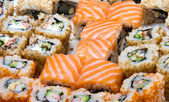 Sushi set turned into salmon with soy sauce in the bottle — Stock Photo