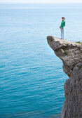 Young slim lonely woman standing at the edge of mountain cliff — Stock Photo