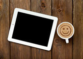 Tablet and coffee with smile sign — Stock Photo
