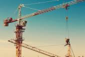 Tower crane lifting up a cement bucket at construction area — Stock Photo