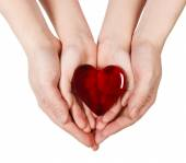 Mother's hands holding baby hands with heart — Stock Photo