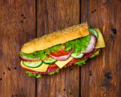 Sandwich with meat and vegetables on wood — Stock Photo