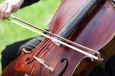 Man's hands playing violoncello outdoors — Stock Photo