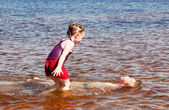 Girl and boy swimming in the lake — Stock Photo