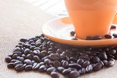 Coffee beans and Cup of coffee on brown fabric paper — Stock Photo