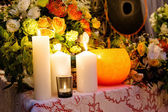 Big white candles on flowers background — Stock Photo