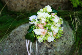 Wedding bouquet on rock — Stock Photo