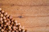 Chopping board with line of hazelnuts. — Stock Photo