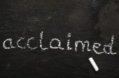 The word acclaimed written with chalk on black stone. — Stock Photo