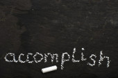 The word accomplish written with chalk on black stone. — Stock Photo