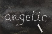 The word angelic written with chalk on black stone. — Stock Photo