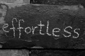 The word EFFORTLESS written with chalk on black stone. — Stock Photo