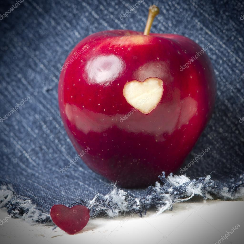 Fresh red apple with a heart shaped cut-out on jeans background ...