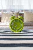 Green alarm clock on bed — Stock Photo
