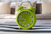 Modern green alarm clock on bed — Stock Photo