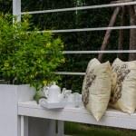 Tea set and yellow pillows on white bench — Stock Photo #61715373