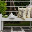 White bench with tea set and pillows — Stock Photo #61715655