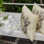 Tray of tea set and pillows on white bench — Stock Photo #61717909