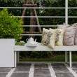 Bench in garden with tea set and pillows — Stock Photo #61717949