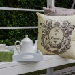 Tray of white tea set with pillows on bench — Stock Photo #61717955