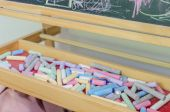 Multicoloured chalk in tray and chalkboard — Stok fotoğraf