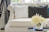 Vazoda sarı çiçek ile lüks beyaz kanepe oturma odasında — Stok fotoğraf