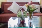 Vaso di vetro del fiore sul tavolo di vetro con divano in legno — Foto Stock