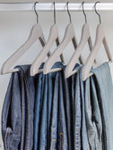 Row of blue jeans on hangers — Stock Photo