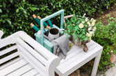 Gardening tools on white wooden table and bench — Stock Photo