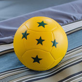 Yellow ball with green five star on bed — Stock Photo