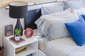 Blue pillow on modern bed with black lamp on white table — Foto de Stock