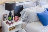 синяя подушка на современной кровати с черной лампой на белом столе — Стоковое фото