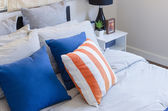 Orange and blue color pillows on bed  — Stock Photo