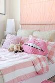 Mädchens Schlafzimmer in rosa Farbe mit Kissen und Puppe — Stockfoto