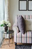 Barevné gauč s polštáři a skleněný stůl v obývacím pokoji — Stock fotografie