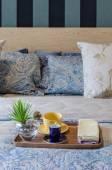 Деревянный поднос чашки чая и завода на кровати — Стоковое фото