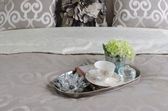 Tray of tea cup and vase of flower on bed  — Stock Photo
