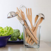 Utensils in glass bottle on kitchen's counter  — Photo