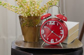 Modern alarm clock on tray with book and plant — Stock Photo
