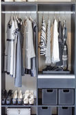 Black and white clothes in black closet  — Stock Photo