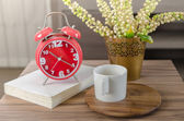 Modern red alarm clock on book with cup on wood tray  — Stock Photo