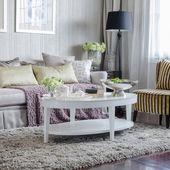 Lyxiga vardagsrum med soffa och vitt bord på mattan — Stockfoto