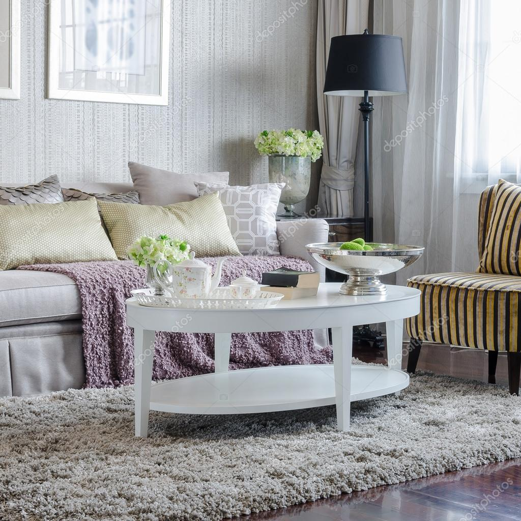 Lyxiga vardagsrum med soffa och vitt bord på mattan ...